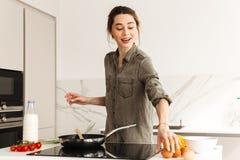Портрет радостной счастливой женщины варя здоровый завтрак с fr Стоковые Фото
