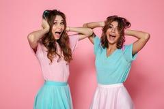 Портрет 2 радостных девушки одел в красочных одеждах Стоковое фото RF