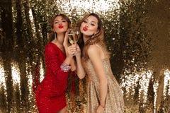 Портрет 2 радостных милых девушек в сияющих платьях Стоковые Изображения RF