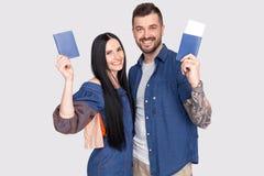 Портрет радостных радостных пар держа паспорт с билетами летания в руках смотря камеру изолированную на яркой серой предпосылке стоковая фотография