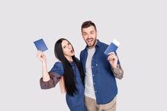 Портрет радостных радостных пар держа паспорт с билетами летания в руках смотря камеру изолированную на яркой серой предпосылке стоковые изображения rf