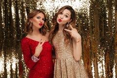 Портрет 2 радостных счастливых женщин в sparkly платьях стоковые изображения