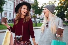 Портрет 2 радостных усмехаясь девушек держа хозяйственные сумки Стоковое Изображение