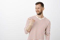 Портрет раздражанного не поддавшийся эмоциям парня в вскользь обмундировании, хмурясь и указывая ОН назад или вышел, выражающ нел Стоковое Изображение RF
