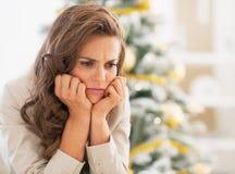 Портрет разочарованной молодой женщины около рождественской елки Стоковая Фотография RF