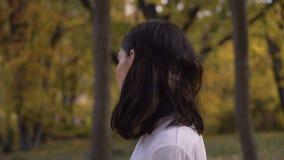 Портрет расстроенной женщины Девушка в парке осени на предпосылке деревьев, женщина выходит рамка 4K сток-видео