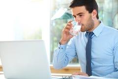 Портрет расслабленного молодого бизнесмена сидя в ярком offi Стоковые Фотографии RF
