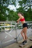 Портрет расслабленной молодой женщины фитнеса на деревянном мосте в парке Стоковые Фотографии RF