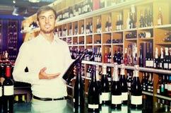 Портрет радостного мужского клиента принимая бутылку вина в магазине Стоковые Изображения RF