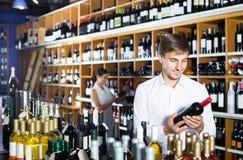 Портрет радостного мужского клиента принимая бутылку вина в магазине Стоковые Фотографии RF