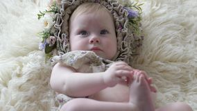 Портрет ребенка в обруче с цветками лежит на половике и представляет на камере на photoshoot видеоматериал