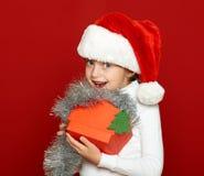 Портрет ребенка девушки с подарочной коробкой на красном цвете, концепции праздника рождества Стоковые Изображения