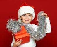 Портрет ребенка девушки с подарочной коробкой на красном цвете, концепции праздника рождества Стоковые Фото