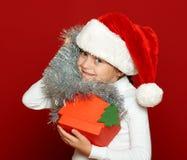 Портрет ребенка девушки с подарочной коробкой на красном цвете, концепции праздника рождества Стоковое Изображение
