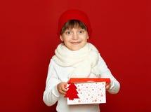 Портрет ребенка девушки с подарочной коробкой на красном цвете, концепции зимнего отдыха Стоковое Изображение RF