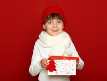 Портрет ребенка девушки с подарочной коробкой на красном цвете, концепции зимнего отдыха Стоковые Изображения