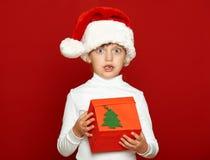Портрет ребенка девушки с подарочной коробкой на красном цвете, концепции праздника рождества Стоковое фото RF