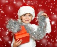 Портрет ребенка девушки с подарочной коробкой на красном цвете, концепции праздника рождества Стоковое Фото
