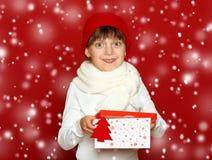 Портрет ребенка девушки с подарочной коробкой на красном цвете, концепции зимнего отдыха Стоковая Фотография RF