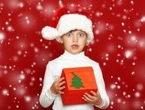 Портрет ребенка девушки с подарочной коробкой на красном цвете, концепции праздника рождества Стоковое Изображение RF
