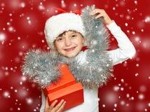 Портрет ребенка девушки с подарочной коробкой на красном цвете, концепции праздника рождества Стоковая Фотография