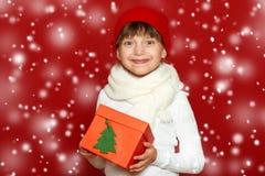 Портрет ребенка девушки с подарочной коробкой на красном цвете, концепции зимнего отдыха Стоковое Изображение