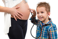Портрет ребенка и беременной женщины Слушает к что идет дальше в мой живот ` s матери Стоковое Изображение