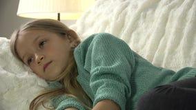 Портрет ребенка смотря ТВ, дистанционное управление пользы девушки, ребенк ослабляя на софе, тренера видеоматериал
