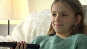 Портрет ребенка смотря ТВ, ослаблять стороны маленькой девочки усмехаясь на софе, тренере акции видеоматериалы