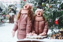 Портрет рождества играть 2 счастливый сестер внешний в городе зимы снежном украшенном на праздники Нового Года стоковое изображение