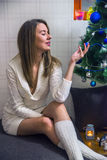 Портрет рождественской елки счастливой молодой женщины расслабляющей близко Усмехаясь молодая женщина около рождественской елки Стоковая Фотография
