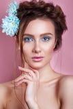 Портрет романтичной молодой женщины при голубой цветок смотря камеру на голубой предпосылке Фото моды весны Воодушевленность spri Стоковые Фотографии RF