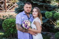 Портрет романтичной пары против предпосылки зеленых кустов и деревьев, девушки держа цветки в руках, молодой красивой невесте Стоковое Изображение RF