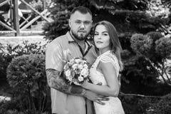 Портрет романтичной пары против предпосылки зеленых кустов и деревьев, девушки держа цветки в руках, молодой красивой невесте Стоковые Изображения