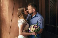 Портрет романтичных пар, человека и женщины целуя в драматическом свете, девушки держа цветки в руках, молодой красивой невесте в Стоковое Изображение RF