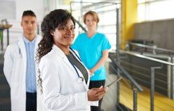 Портрет дружелюбных женских Афро-американских доктора и команды в ярком современном офисе Стоковое фото RF