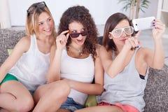 Портрет 3 друзей принимая фото с smartphone Стоковые Изображения RF