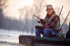 Портрет рыболова с рыболовной удочкой сидит на замороженном реке в th стоковая фотография rf