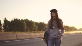 Портрет рыжеволосой девушки в наушниках с скейтбордом в руках идя вдоль обочины вдоль дезертированное сток-видео