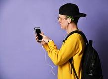 Портрет рюкзака жизнерадостного студента нося, в крышке и стеклах и смартфоне использования над пурпурной предпосылкой стоковая фотография rf
