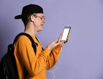 Портрет рюкзака жизнерадостного студента нося, в крышке и стеклах и смартфоне использования над пурпурной предпосылкой стоковое изображение rf