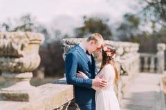 Портрет свадьбы стильных пар новобрачных представляя на старом каменном парке террасы весной и любяще касаясь мимо стоковое фото rf
