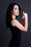 Портрет сексуального тайного агента женщины представляя с оружием над серым цветом Стоковые Фото