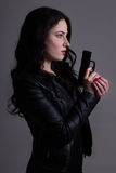 Портрет сексуальной женщины в черноте с оружием над серым цветом Стоковые Изображения