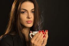 Портрет сексуальной женщины наслаждаясь горячей чашкой чаю на темном backg Стоковая Фотография