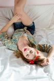 Портрет сексуальной молодой красивой белокурой женщины в рубашке печати цветка шортов джинсов имея потеху кладя ее ноги на стену  Стоковые Изображения RF