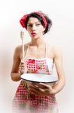 Портрет сексуальной привлекательной девушки pinup держа шар и ложку & смотря камеру любознательную на белизне или космосе экземпл стоковое изображение rf