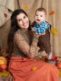 Портрет семьи в сезоне осени Женщина и мальчик сидят на желтых листьях, яблоках, тыкве и украшении падения Стоковые Фото