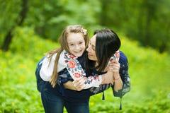 Портрет семьи девушки и матери в парке на предпосылке стоковая фотография