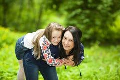 Портрет семьи девушки и матери в парке на предпосылке стоковые фото